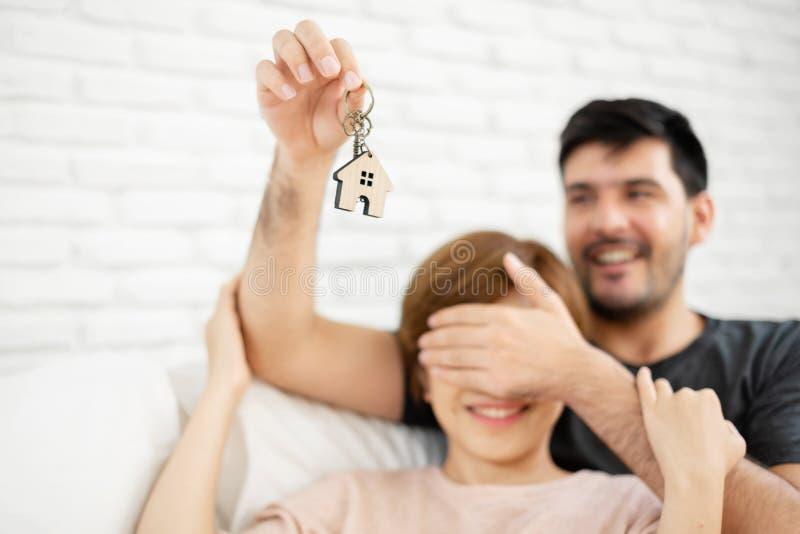 Bemannen Sie überraschende Frau mit einem Schlüssel ihres neuen Hauses lizenzfreies stockbild