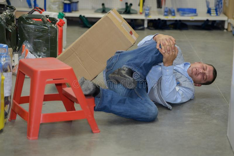 Bemannen Sie Arbeitskraft mit Knieverletzungs-Konzeptarbeitsunfall stockfoto