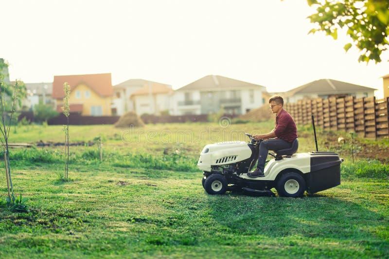bemannen Sie Arbeitskraftausschnittgras mit Rasenmäher, lawncare Konzept Industrielle Sonderkommandos lizenzfreies stockbild