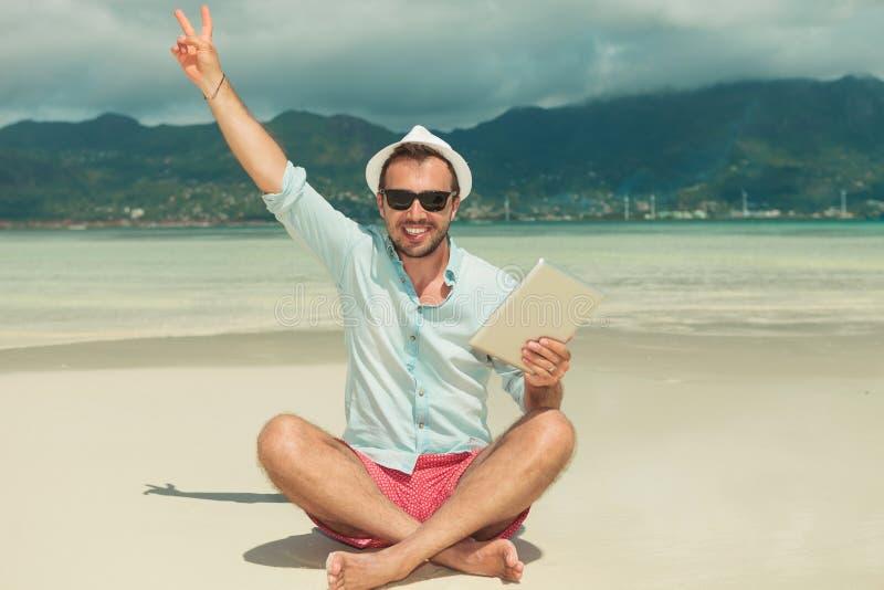 Bemannen Sie auf dem Strand mit dem ipad in der Hand sitzen, das Siegeszeichen zeigt lizenzfreie stockfotos