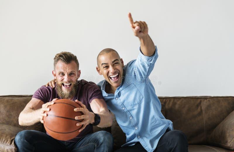 Bemannen Sie auf einem aufpassenden Sport der Couch zusammen sitzen stockfotografie