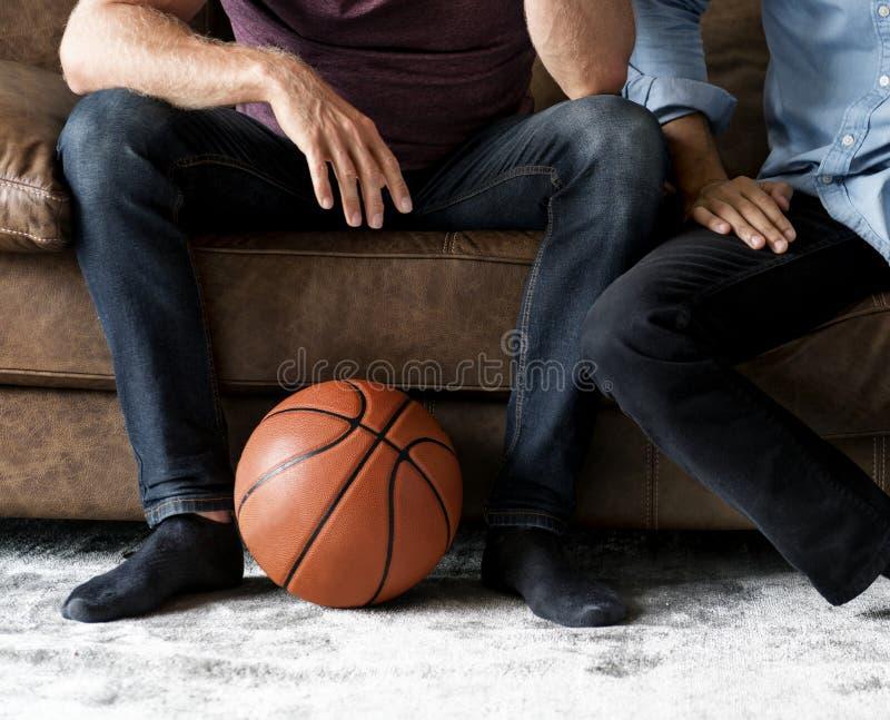 Bemannen Sie auf einem aufpassenden Sport der Couch zusammen sitzen stockbilder