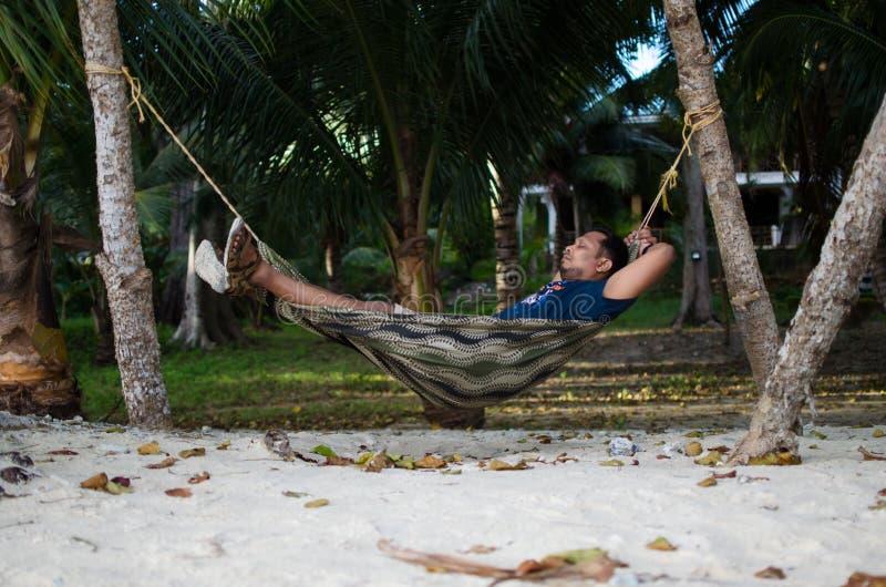 Bemannen Sie auf einer Hängematte schlafen oder ein Netz nahe auf einem Strand stockbild