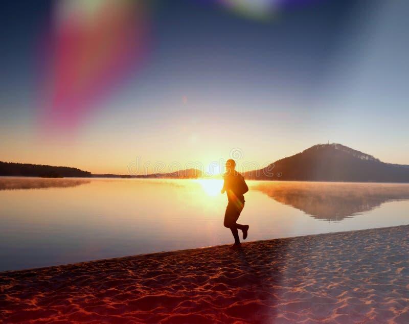 Bemannen Sie Betrieb auf Strand gegen Hintergrund eines schönen Sonnenuntergangs Sand von Gebirgssee stockfotografie
