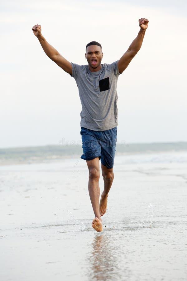 Bemannen Sie Betrieb barfuß auf Strand mit den Armen, die in Sieg angehoben werden stockbild