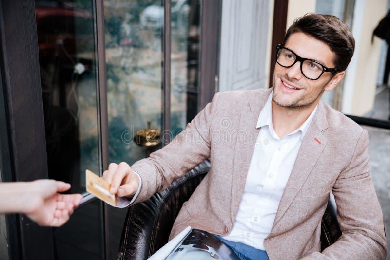 Bemannen Sie Café mit Kreditkarte sitzen im im Freien und zahlen stockbild