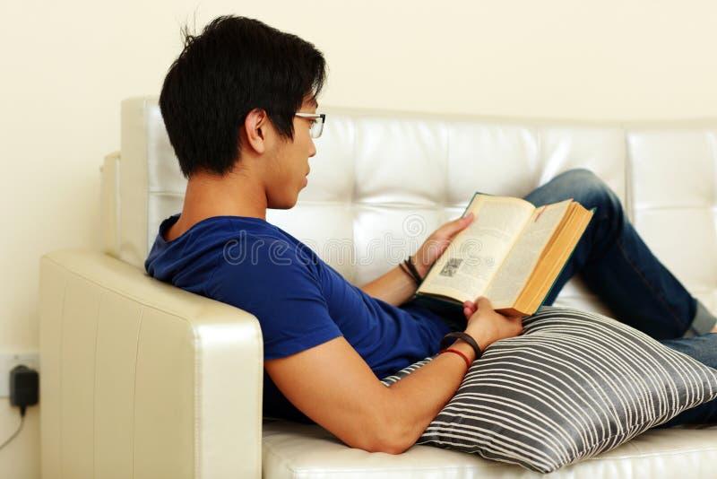 Bemannen Sie das Ablesen eines Buches bei der Entspannung auf Sofa stockfotos
