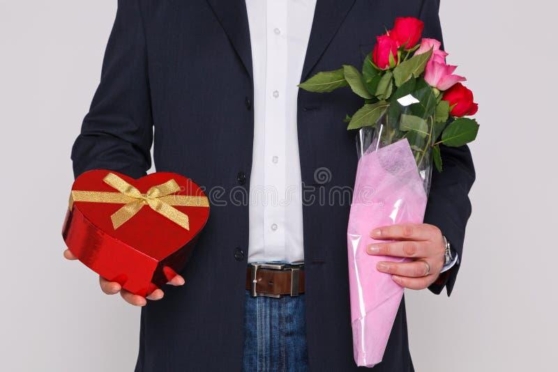 Bemannen Sie das Anhalten der Blumen und des Kastens Schokoladen stockfotografie
