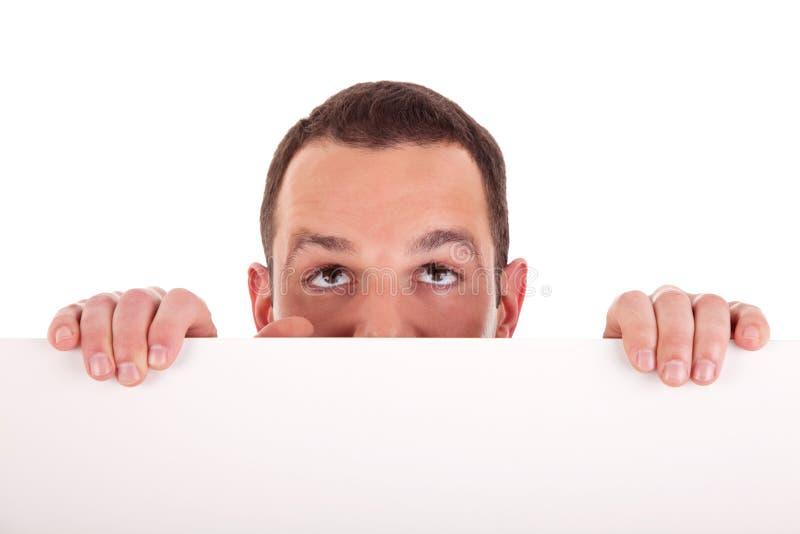 Bemannen Sie das Anhalten eines weißen Vorstands und oben schauen stockfotos