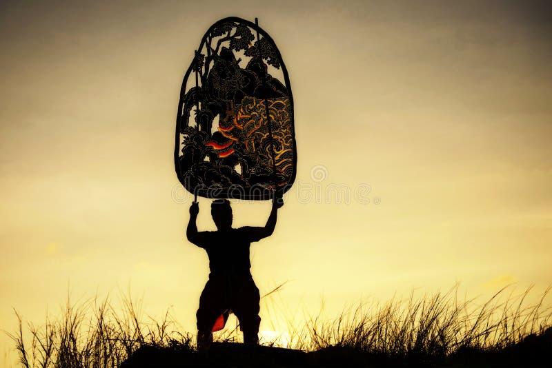 bemannen Sie das Anheben der thailändischen Schattenengelsmarionette an der Bergspitzeklippe lizenzfreie stockfotos