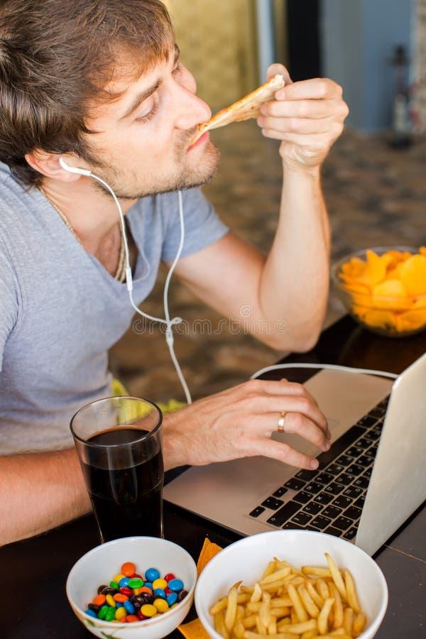 Bemannen Sie das Arbeiten am Computer und das Essen des Schnellimbisses Ungesunde Lebensdauer lizenzfreie stockfotos