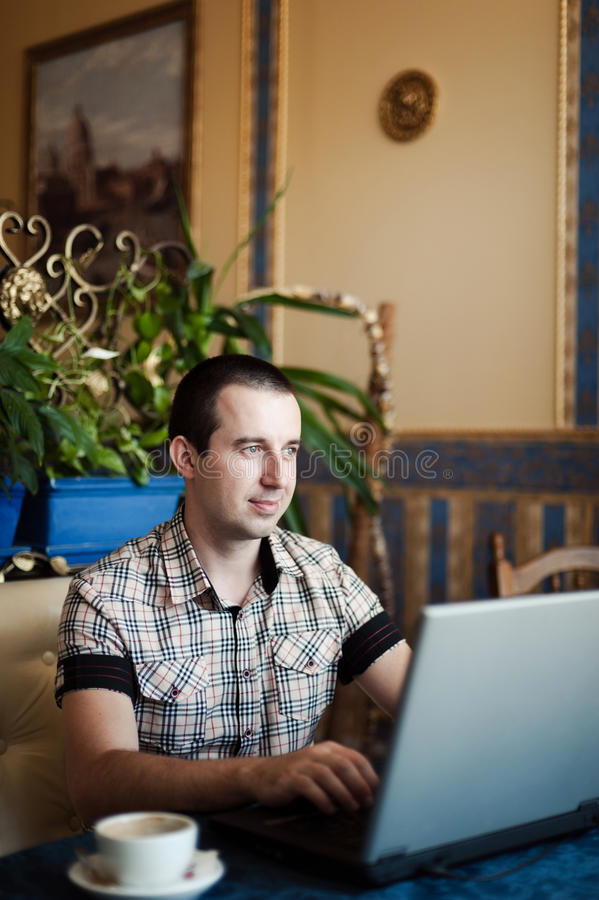Bemannen Sie das Arbeiten in einem Café auf einem Laptop stockbilder