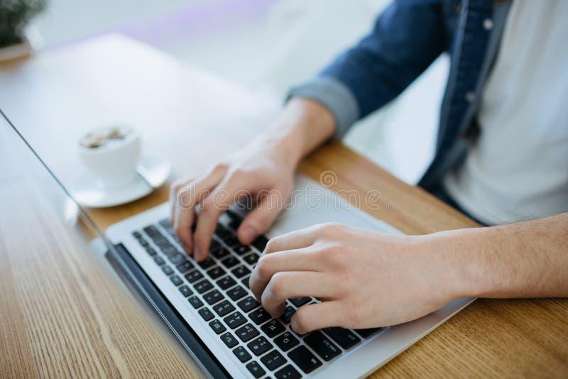 Bemannen Sie das Arbeiten an einem macbook oder einem Laptop im Café stockbilder
