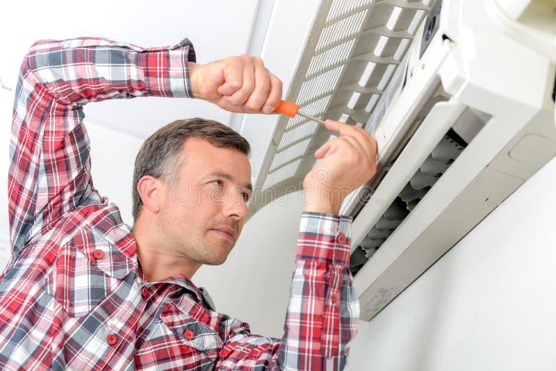 Bemannen Sie das Arbeiten an Klimaanlage, die offene Klappe stockfotografie