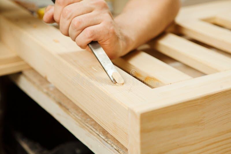Bemannen Sie das Arbeiten mit dem Schnitzen der Ausrüstung in der Werkstatt, die Meißel hält lizenzfreies stockfoto