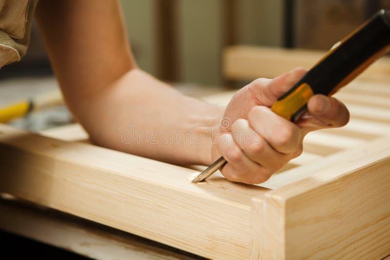 Bemannen Sie das Arbeiten mit dem Schnitzen der Ausrüstung in der Werkstatt, die Meißel hält stockfotos