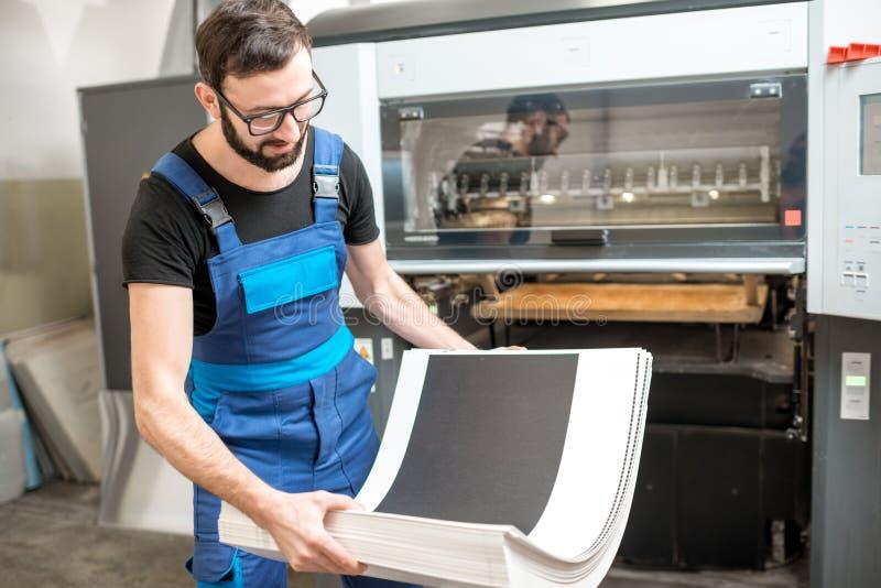 Bemannen Sie das Arbeiten mit Druckmaschine an der Herstellung stockfoto