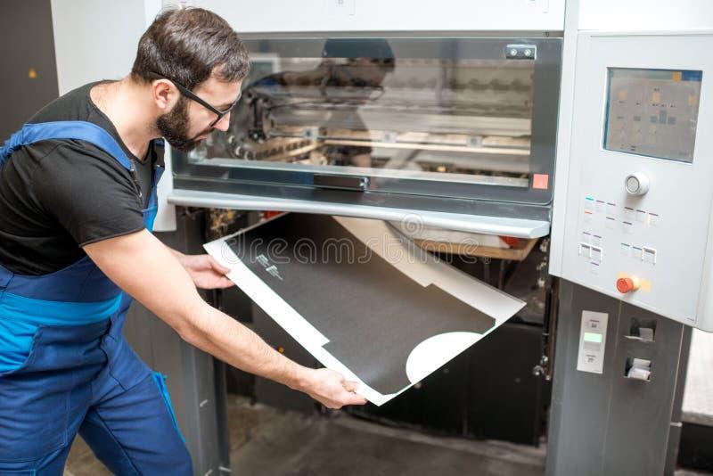 Bemannen Sie das Arbeiten mit Druckmaschine an der Herstellung stockfotografie