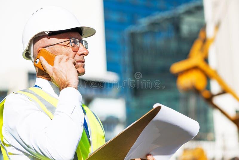 Bemannen Sie das architector, das am Baubereich im Freien ist, der bewegliches Gespräch hat stockbilder