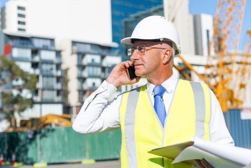 Bemannen Sie das architector, das am Baubereich im Freien ist, der bewegliches Gespräch hat lizenzfreies stockfoto