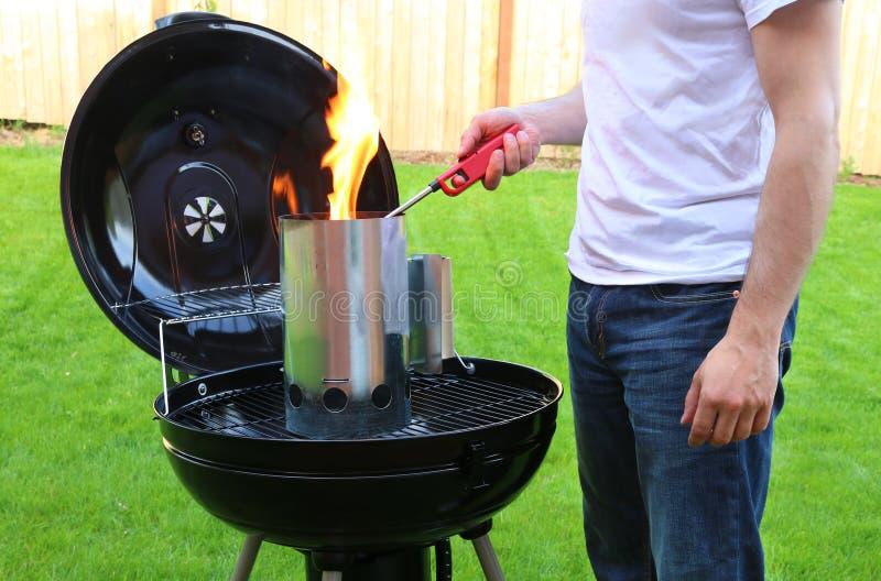 Bemannen Sie das Beginnen des BBQ-Kohlenkaminfeuers mit Feuerzeug stockfoto