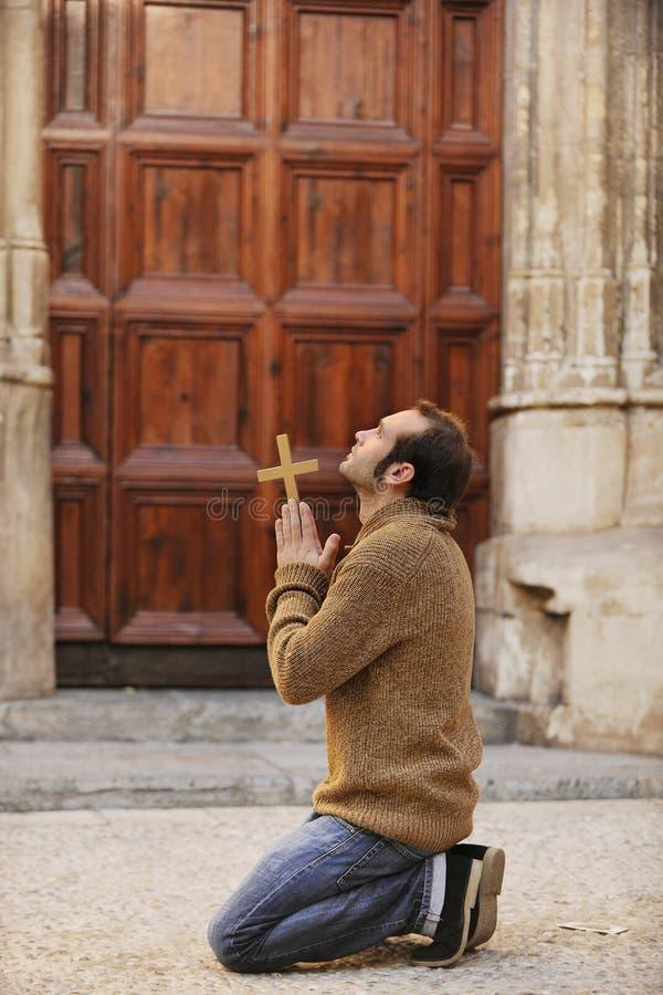 Bemannen Sie das Beten vor der Kirche, die ein Kreuz anhält stockfotos