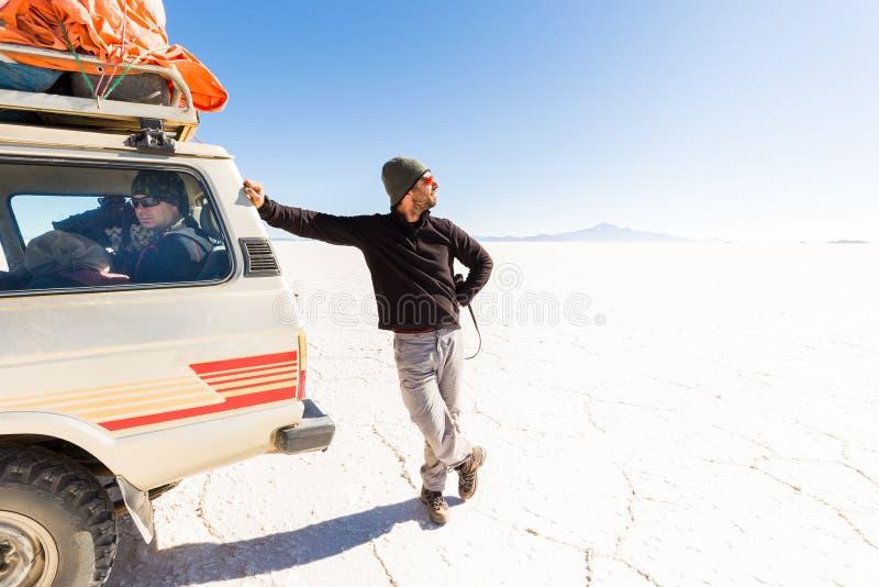 Bemannen Sie das Betrachten der Sonne, SUV, das Salar De Uyuni-Wüste fährt lizenzfreies stockfoto