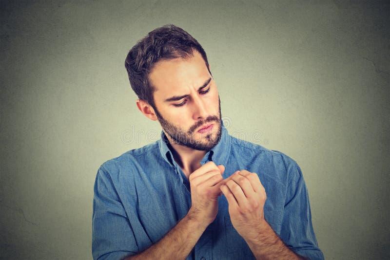 Bemannen Sie das Betrachten von den Handnägeln, die über Sauberkeitsmikroben besessen sind lizenzfreie stockbilder