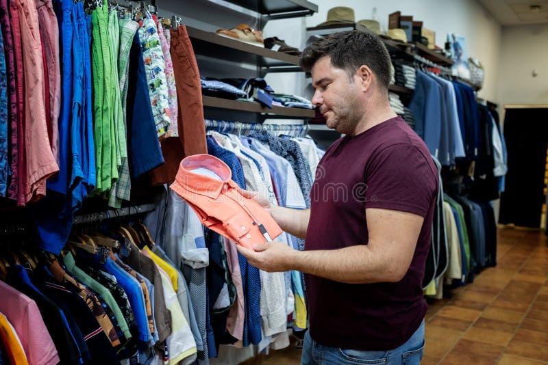 Bemannen Sie das Betrachten von Hemden, von Jacken und von Schuhen stockfotos