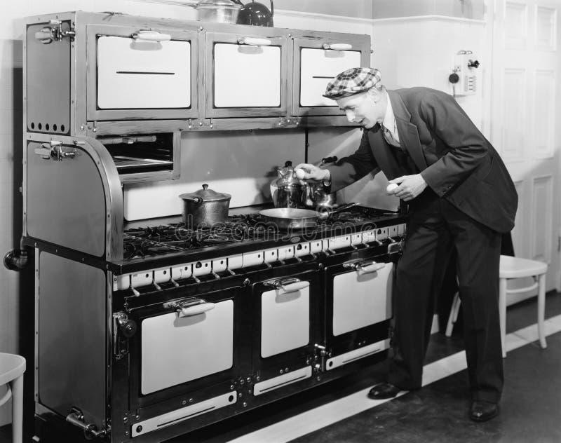 Bemannen Sie das Brechen des Eies in eine Bratpfanne in der Küche (alle dargestellten Personen sind nicht längeres lebendes und k stockbilder