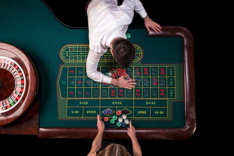 Bemannen Sie das Croupier und Frau, die Roulette am Tisch im Kasino spielen Draufsicht an einem grünen Tisch der Roulette mit ein lizenzfreie stockfotos