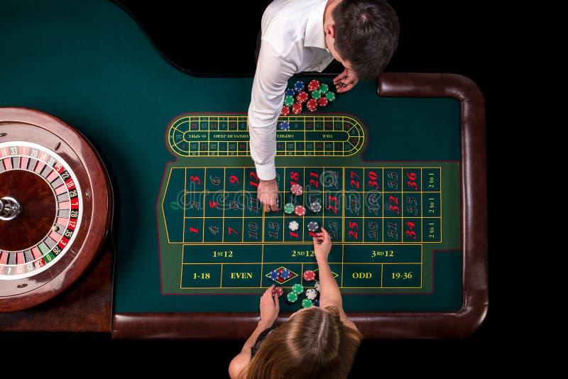 Bemannen Sie das Croupier und Frau, die Roulette am Tisch im Kasino spielen Draufsicht an einem grünen Tisch der Roulette mit ein stockfoto
