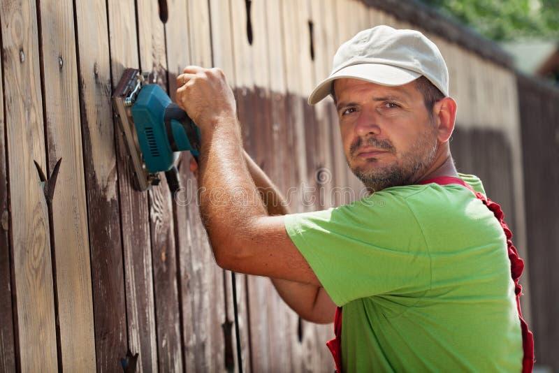 Bemannen Sie das Entfernen der alten gebrochenen Farbe von einem Zaun lizenzfreies stockbild