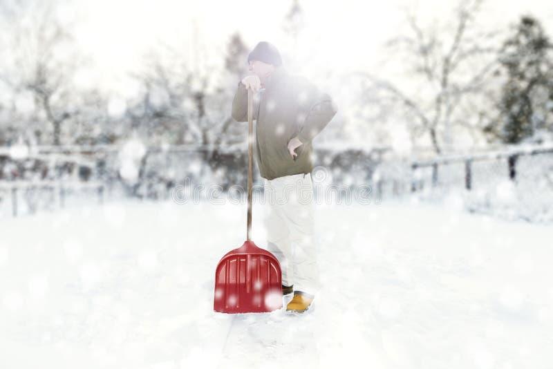 Bemannen Sie das Entfernen des Schnees auf dem Hinterhof mit der Schaufel während der Schneefälle lizenzfreies stockfoto