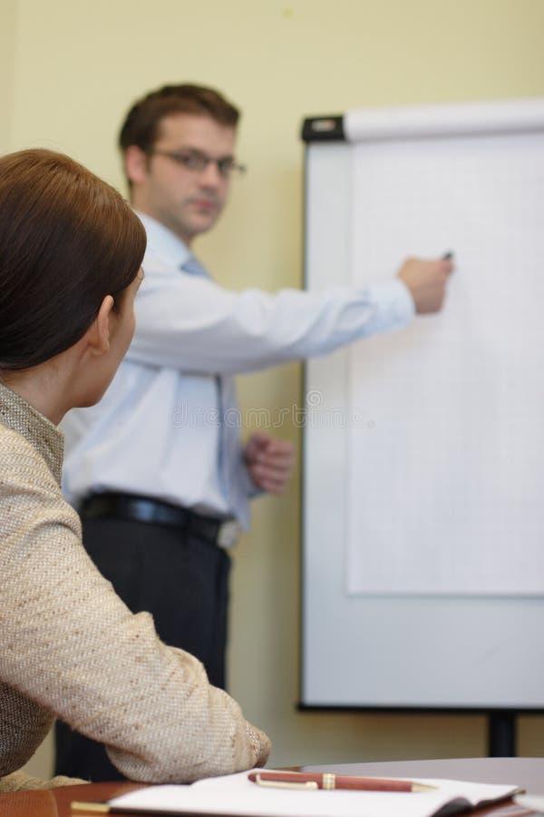 Bemannen Sie das Erklären einer Idee auf Flip-Chart Frau lizenzfreies stockfoto