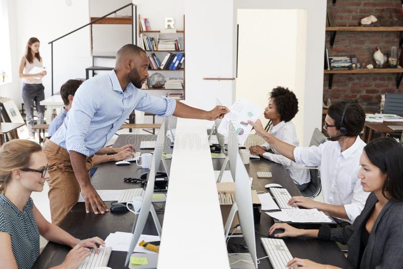 Bemannen Sie das Führen des Dokuments über Schreibtisch in einem beschäftigten Bürogroßraum stockbilder