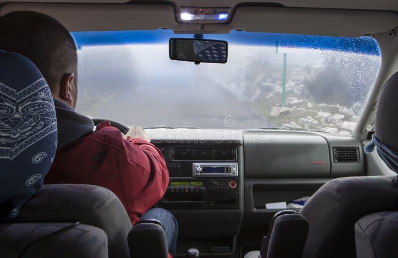 Bemannen Sie das Fahren durch schmale Gebirgsstraße mit dichtem Nebel stockfotografie