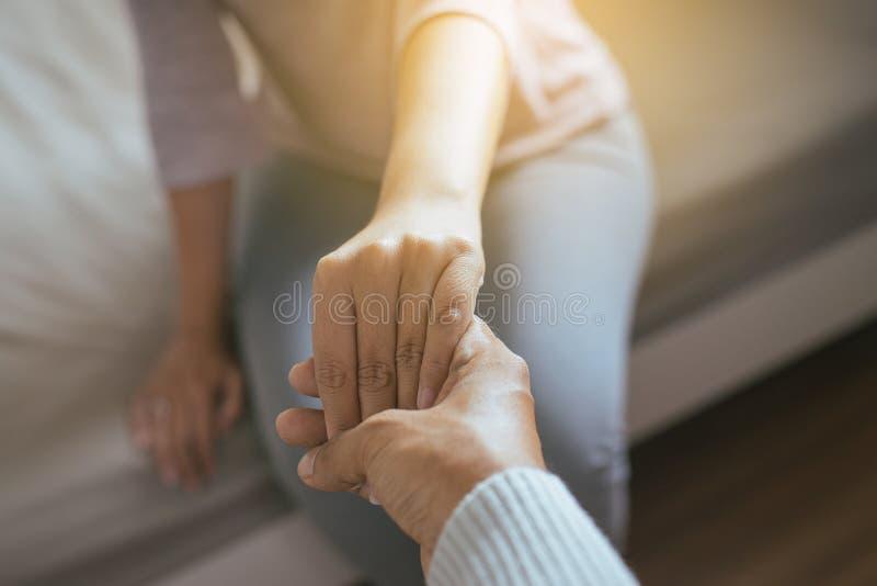 Bemannen Sie das Geben deprimierter Frau, Psychiatershändchenhaltenpatient, Meantal-Gesundheitswesenkonzept der Hand stockfotografie