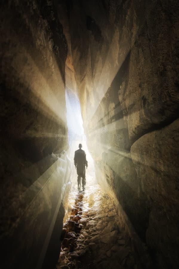 Bemannen Sie das Gehen aus einer Höhle heraus in das Licht stockfotos