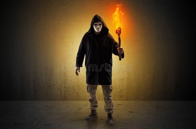 Bemannen Sie das Gehen in einen leeren Raum mit brennendem Flambeau stockbilder