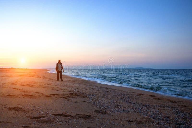 Bemannen Sie das Gehen entlang den Strand während einer schönen Sonnenuntergangentspannungszeit stockfoto