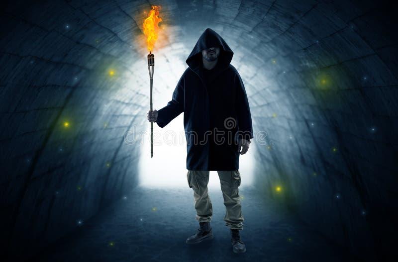 Bemannen Sie das Gehen mit brennendem Flambeau in einem dunklen Tunnel stockbilder