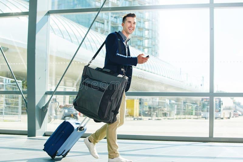 Bemannen Sie das Gehen mit Gepäck und Telefon beim Stationslächeln lizenzfreie stockbilder