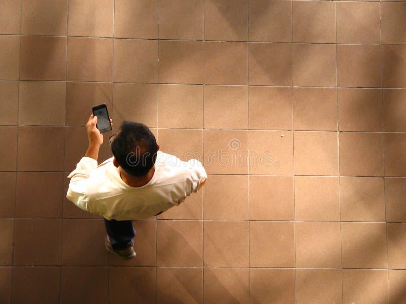 Bemannen Sie das Gehen und das Simsen am Handy, Vogelperspektive lizenzfreie stockfotos