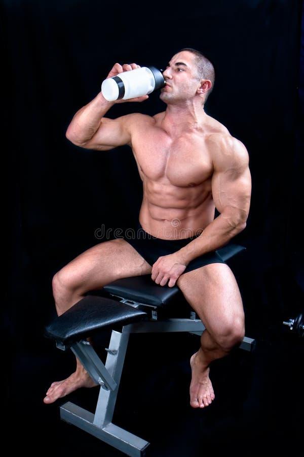 Bemannen Sie das Genießen einer Flasche Wassers nach Übung stockfotos