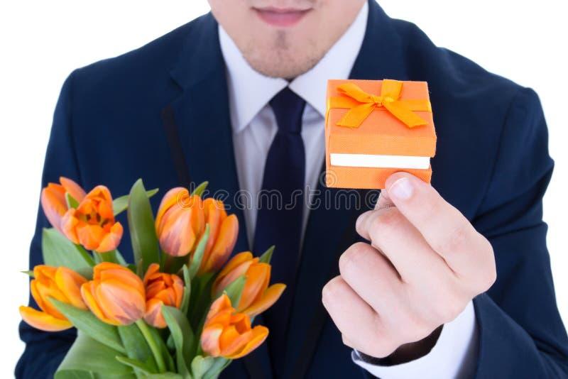 Bemannen Sie das Halten der Geschenkbox mit dem Ehering und Blumen, die auf w lokalisiert werden lizenzfreie stockfotos