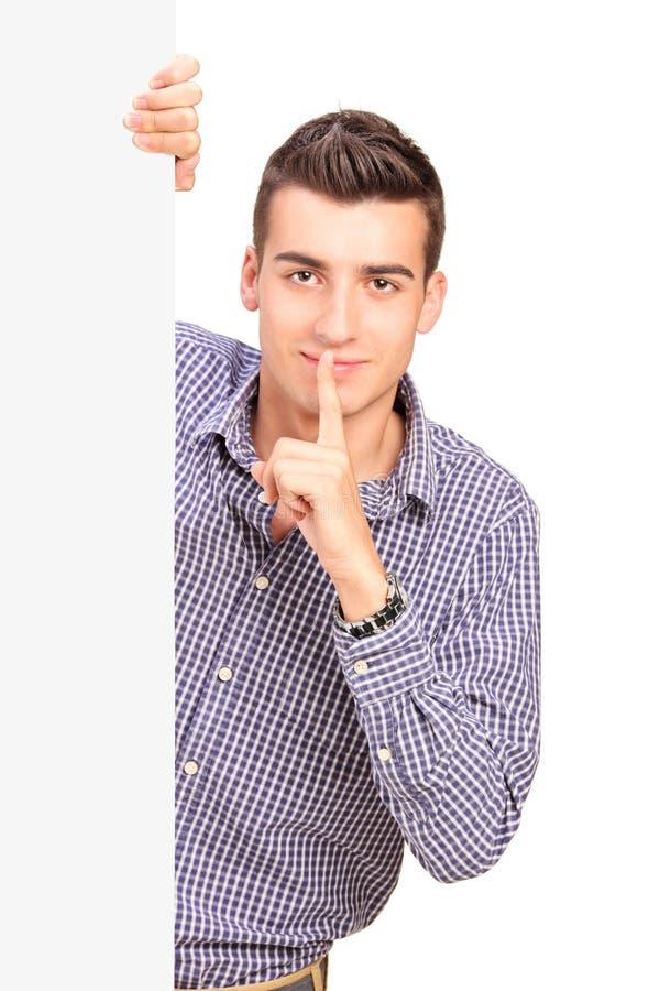 Bemannen Sie das Halten des Fingers auf Lippen hinter Leerplatte lizenzfreies stockbild