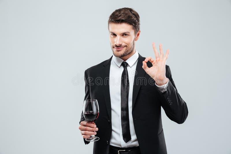 Bemannen Sie das Halten des Glases Rotweins und das Zeigen des okayzeichens stockfotografie