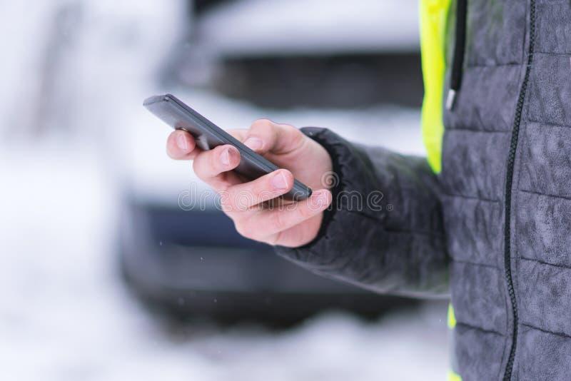 Bemannen Sie das Halten des Handys und das Nennen von Winterautodienstleistungen, um zu helfen lizenzfreie stockbilder