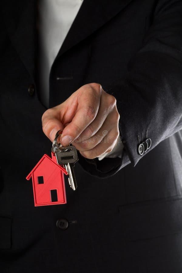 Bemannen Sie das Halten des Haustürschlüssels mit rotem Hausschlüsselanhängeranhänger stockbild